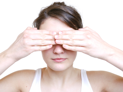 woman covering her eyes with her fingers