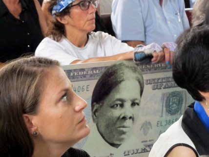 FILE - In this Monday, Aug. 31, 2015, file photo, a woman holds a sign supporting Harriet Tubman for the $20 bill during a town hall meeting at the Women's Rights National Historical Park in Seneca Falls, N.Y. A Treasury official said Wednesday, April 20, 2016, that Secretary Jacob Lew has decided to put Harriet Tubman on the $20 bill, making her the first woman on U.S. paper currency in 100 years. (AP Photo/Carolyn Thompson, File)