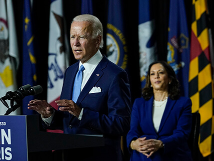Joe Biden speaking at a podium and Kamala Harris seated behind him at a campaign event in August 2020.