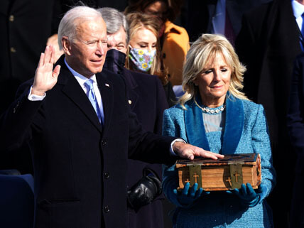 President Biden has his right hand raised and his left hand on top of a bible that Jill Biden is holding.
