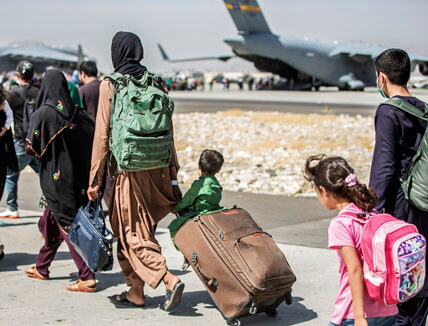 A woman with two small children walks across a runway to a waiting military cargo plane in the background.
